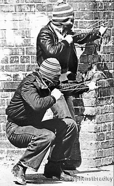 Young hooded men firing catapults, Belfast, Northern Ireland, by Stephen S T Bradley, editorial, commercial, PR and advertising photographer, Dublin, Ireland