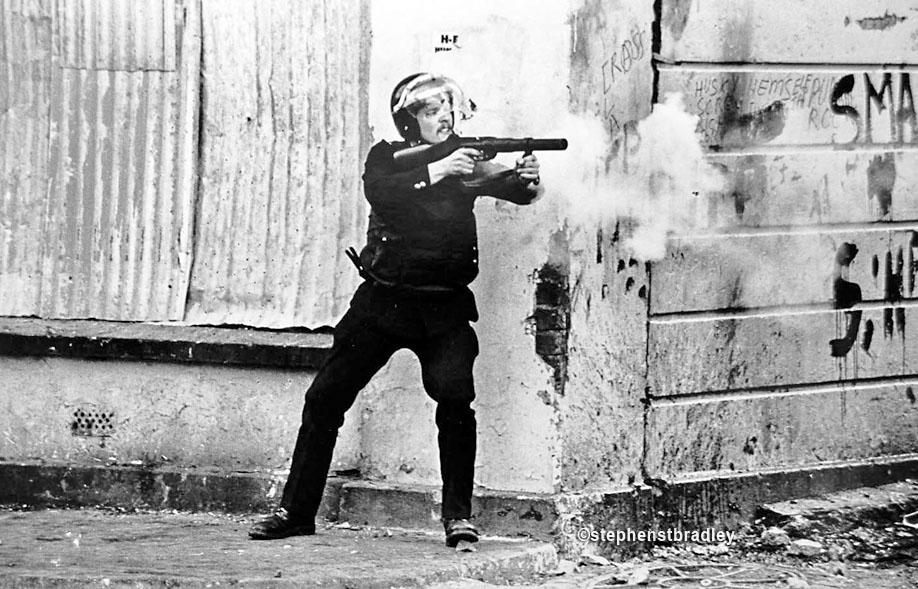 RUC officer firing plastic bullet gun, Ardoyne, Belfast, Northern Ireland, by Stephen S T Bradley, editorial, commercial, PR and advertising photographer, Dublin, Ireland