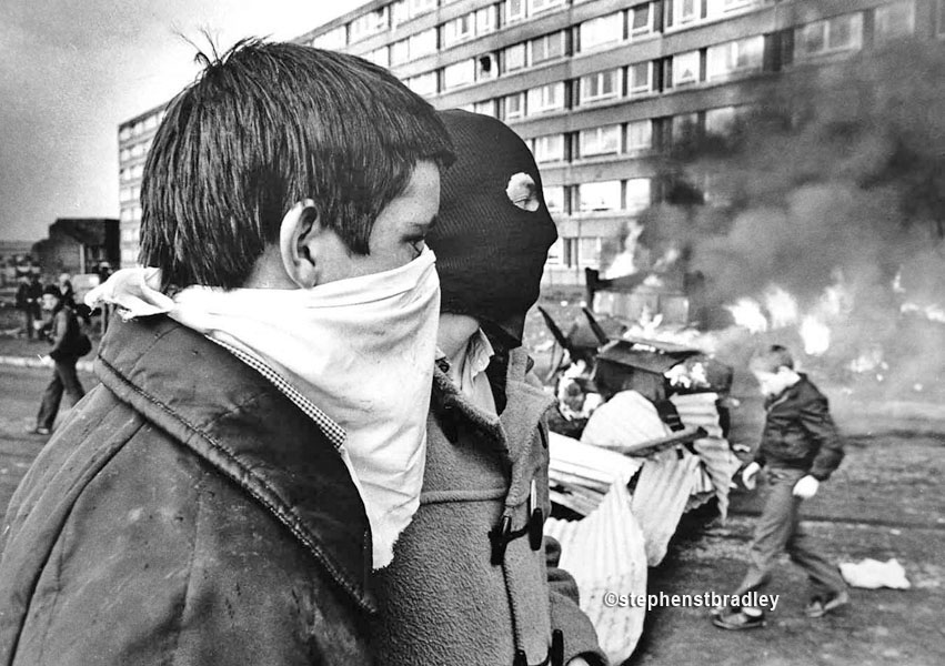 Hooded young men beside burning vehicle, Divis Flats, Belfast, by Stephen S T Bradley, editorial, commercial, PR and advertising photographer, Dublin, Ireland