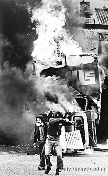 Rioters in front of burning vehicle, Bogside, Derry, Northern Ireland, by Stephen S T Bradley, editorial, commercial, PR and advertising photographer, Dublin, Ireland
